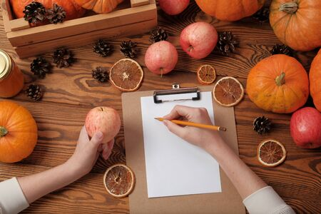 Top view on female hands when she is preparing for recording. Thanksgiving gifts, autumn background, pumpkins, apples, cones, dried oranges on a wooden background, top view, copy space, flat lay Stok Fotoğraf