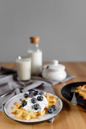 Viennese waffles with ice cream and blueberries with a bottle of milk. side view Reklamní fotografie