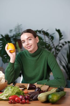 A young girl in a green sweater holds a lemon in her hand. On the table are many different vegetables and fruits, the concept of veganism, vegetarianism, healthy eating, diet.