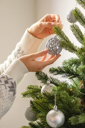 Decorate the Christmas tree with christmas toy. Closeup image of woman in sweater decorating Christmas tree with baubles. The morning before Xmas.