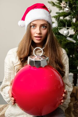 A Christmas.A Young Girl In A Christmas Hat And A White Knitted Sweater With