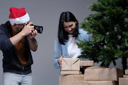 A young guy in a Christmas cap is filming on a mirrorless camera as a young girl with black hair is wrapping Christmas presents. Shooting for blog and vlog. Social Media Videos and Photos. DIY concept