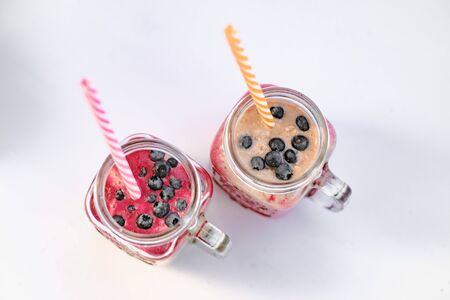 Berry smoothie in two glass jars with straws top view. Healthy breakfast. The concept of healthy eating and dieting.