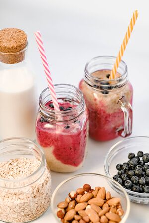 Berry smoothie in two glass jars with straws. Healthy breakfast - milk in a glass jar, oatmeal, almonds and blackberries. The concept of healthy eating and dieting. Stock Photo