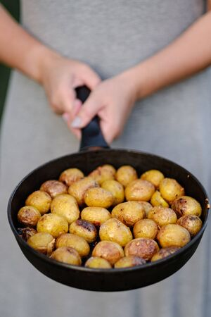 girl holds hands a pan with fried potatoes. top view, close-up camping picnic concept. top view Фото со стока