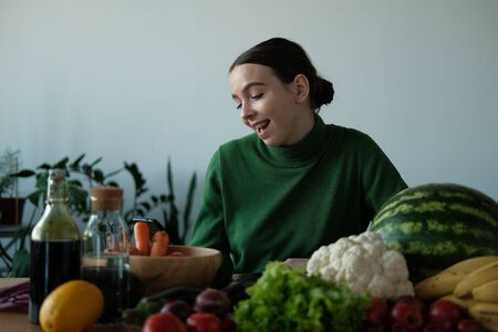 A young girl in a green sweater and Christmas hat is looking for a recipe for cooking on a background of vegetables and fruits. The concept of Christmas and healthy eating. Stock Photo