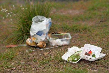 Various plastic trash remains in countryside green meadow. People left trash after the picnic. Environmental pollution. Ecological catastrophe Zdjęcie Seryjne
