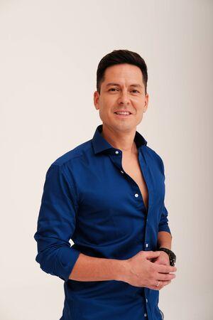 Studio portrait of handsome man in blue shirt on plain background Reklamní fotografie