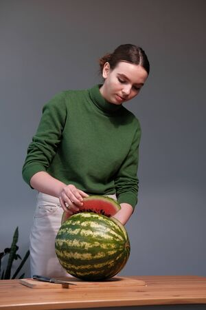 A young girl in a green sweater cuts a watermelon a knife on a cutting wooden board on a gray background. Healthy eating concept 스톡 콘텐츠
