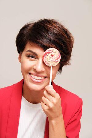 Studio portrait of woman holding colorful lollipop against plain background