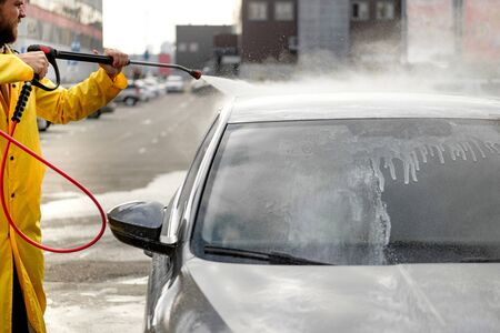 Young man washing his car in car wash. Cleaning Car Using High Pressure Water. Washing with soap. Reklamní fotografie