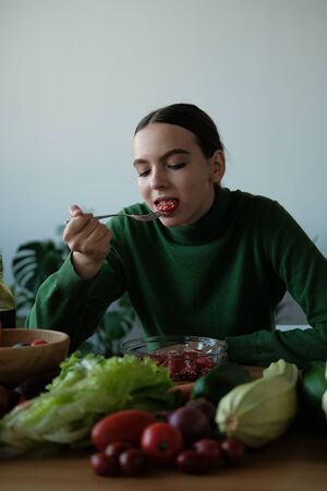 Young woman eating healthy food sitting in the beautiful interior with green flowers on the background. Vegan food concept. World vegan day Stock Photo - 131721541