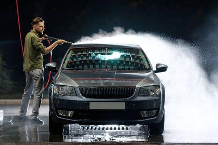 Junger Mann wäscht sein Auto in der Waschanlage. Auto mit Hochdruckwasser reinigen. Waschen mit Seife.