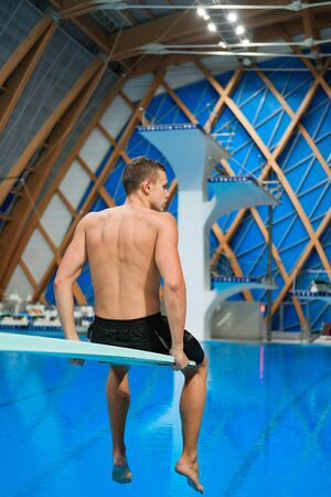 young athlete swimmer sitting on the edge of the platform in an indoor pool Banco de Imagens