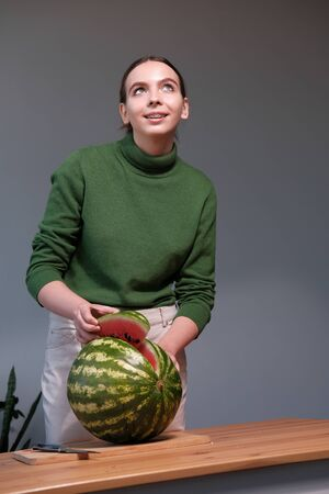 A young girl in a green sweater cuts a watermelon a knife on a cutting wooden board on a gray background. Healthy eating concept Stok Fotoğraf