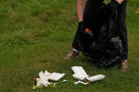 Volunteer man collecting trash from countryside green . Trash-free  concept. Single-use plastic is a human addiction that is destroying our planet Zdjęcie Seryjne