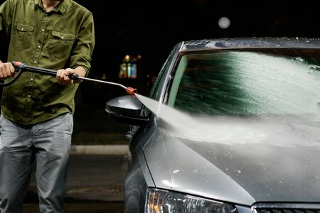 Young man washing his car in car wash. Cleaning Car Using High Pressure Water. Washing with soap. 스톡 콘텐츠