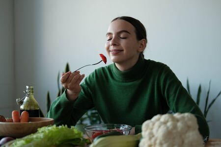 Young woman eating healthy food sitting in the beautiful interior with green flowers on the background. Vegan food concept. World vegan day