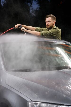 Young man washing his car in car wash. Cleaning Car Using High Pressure Water. Washing with soap. Stockfoto