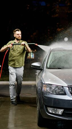 Young man washing his car in car wash. Cleaning Car Using High Pressure Water. Washing with soap. Stok Fotoğraf