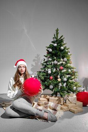 A young girl in a Christmas hat and a white knitted sweater with a large red ball in her hands sits on a plaid against the background of a Christmas tree. Christmas and new year concept. Standard-Bild - 132236410