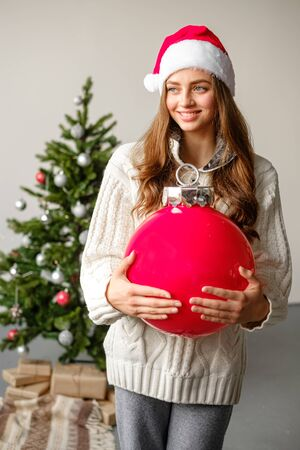 A young girl in a Christmas hat and a white knitted sweater with a big red Christmas ball in her hands is standing against the background of a Christmas tree. Christmas and new year concept. Banco de Imagens