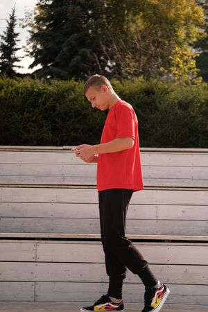 Stylish casual teenage boy in red t-shirt using mobile phone