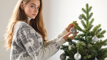 Merry Christmas and Happy Holidays! Young girl in a Christmas sweater with deers decorate the Christmas tree indoors. The morning before Xmas. Standard-Bild - 132236380