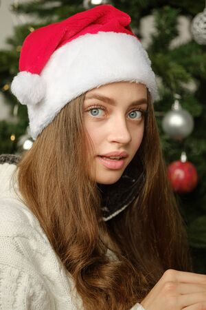 Close-up portrait of a young cute girl in a Christmas hat against the background of the Christmas tree. Christmas and new year concept.