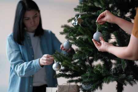 Female hands decorate the Christmas tree. In the background in bokeh a young girl with black hair decorates the Christmas tree with Christmas balls Stock Photo