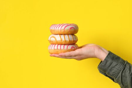 Three donuts in the palm on a yellow background. close-up. Sweets.