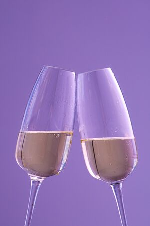 two glasses of champagne on a purple background. sparkling wine. Holiday concept, New Year, wedding, birthday, Christmas.
