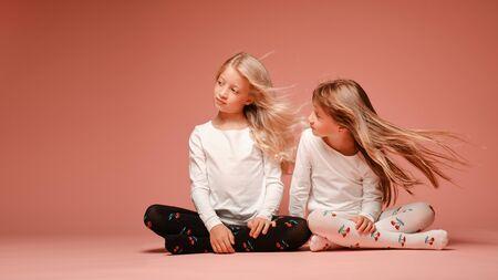 Due bambine carine sono sedute una accanto all'altra su uno sfondo rosa in studio. Capelli svolazzanti al vento. Scuola materna, infanzia, divertimento, concetto di famiglia. Una posa alla moda di due sorelle.