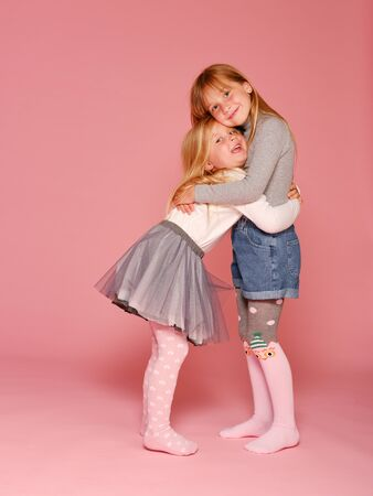 Twee schattige kleine meisjes staan naast elkaar op een roze achtergrond in de studio. Kleuterschool, jeugd, plezier, familieconcept. Twee modieuze zussen poseren. Stockfoto