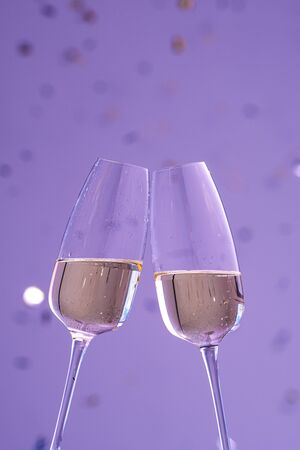 two glasses with champagne on violet with confetti. a sparkling wine. Holiday concept, New Year, wedding, birthday, christmas. Stockfoto