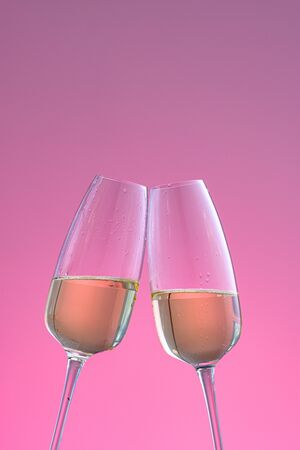 two glasses of champagne on a pink background. a sparkling wine. Holiday concept, New Year, wedding, birthday, christmas.