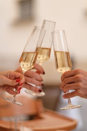 three girls clink glasses of champagne on a beautiful summer terrace. sparkling champagne glasses close-up