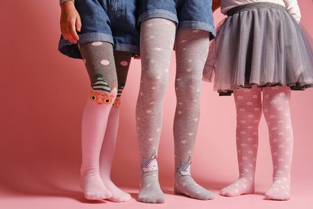Girlish legs in pantyhose on a pink background. A collection of childrens tights for girls. A variety of knitted tights. Childrens clothes. Childrens fashion. Legs and feet of a group of girls