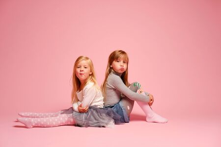 Dwie śliczne dziewczynki siedzą obok siebie na różowym tle w studio. Przedszkole, dzieciństwo, zabawa, koncepcja rodziny. Dwie modne siostry pozowanie. Zdjęcie Seryjne