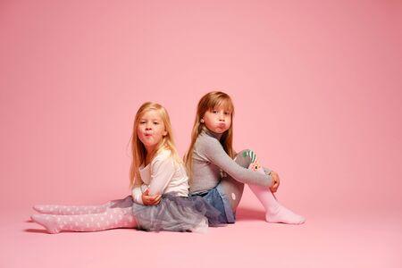 Zwei süße kleine Mädchen sitzen nebeneinander auf rosafarbenem Hintergrund im Studio. Kindergarten, Kindheit, Spaß, Familienkonzept. Zwei modische Schwestern posieren. Standard-Bild