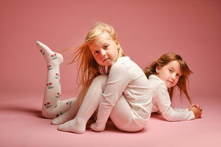 Deux jolies petites filles posant sur fond rose en studio. Jardin d'enfants, enfance, amusement, concept de famille. Deux soeurs à la mode posant.