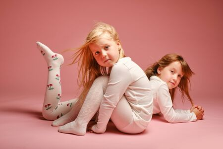 Two cute little girls posing on a pink background in the studio. Kindergarten, childhood, fun, family concept. Two fashionable sisters posing. Stockfoto - 132920284