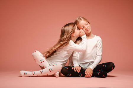 Dos niñas lindas secretan entre sí sobre un fondo rosa en el estudio. Jardín de infantes, infancia, diversión, concepto de familia. Dos hermanas de moda posando. Chisme Foto de archivo