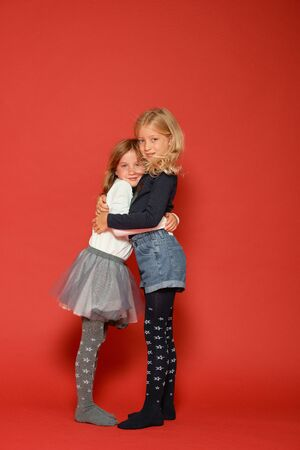 children posing on a red background in the studio. Kindergarten, childhood, fun, family concept.