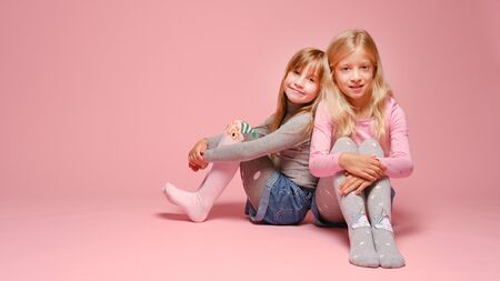 Two cute little girls are sitting next to each other on a pink background in the studio. Kindergarten, childhood, fun, family concept. Two fashionable sisters posing. Stockfoto
