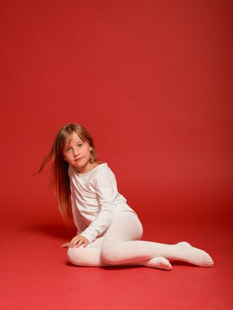 Cute little girl posing on a red background in the studio. Kindergarten, childhood, fun, family concept. Childrens fashion
