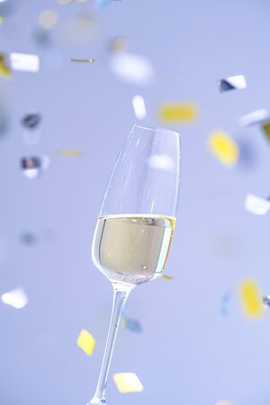 two glasses with champagne on a blue background with confetti. a sparkling wine. Holiday concept, New Year, wedding, birthday, christmas. 版權商用圖片