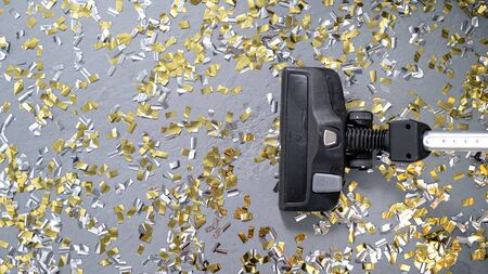 Vacuum cleaner cleans up bright confetti. the party is over. House cleaning. close-up. top view.