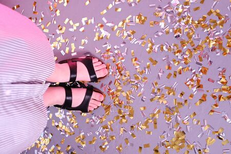 Confetti on a gray concrete floor after a party with a girl's legs, top view