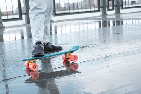 Young skateboarder in dark sneakers and jeans standing on a skateboard. Fragment of a penny board and legs close-up. 版權商用圖片
